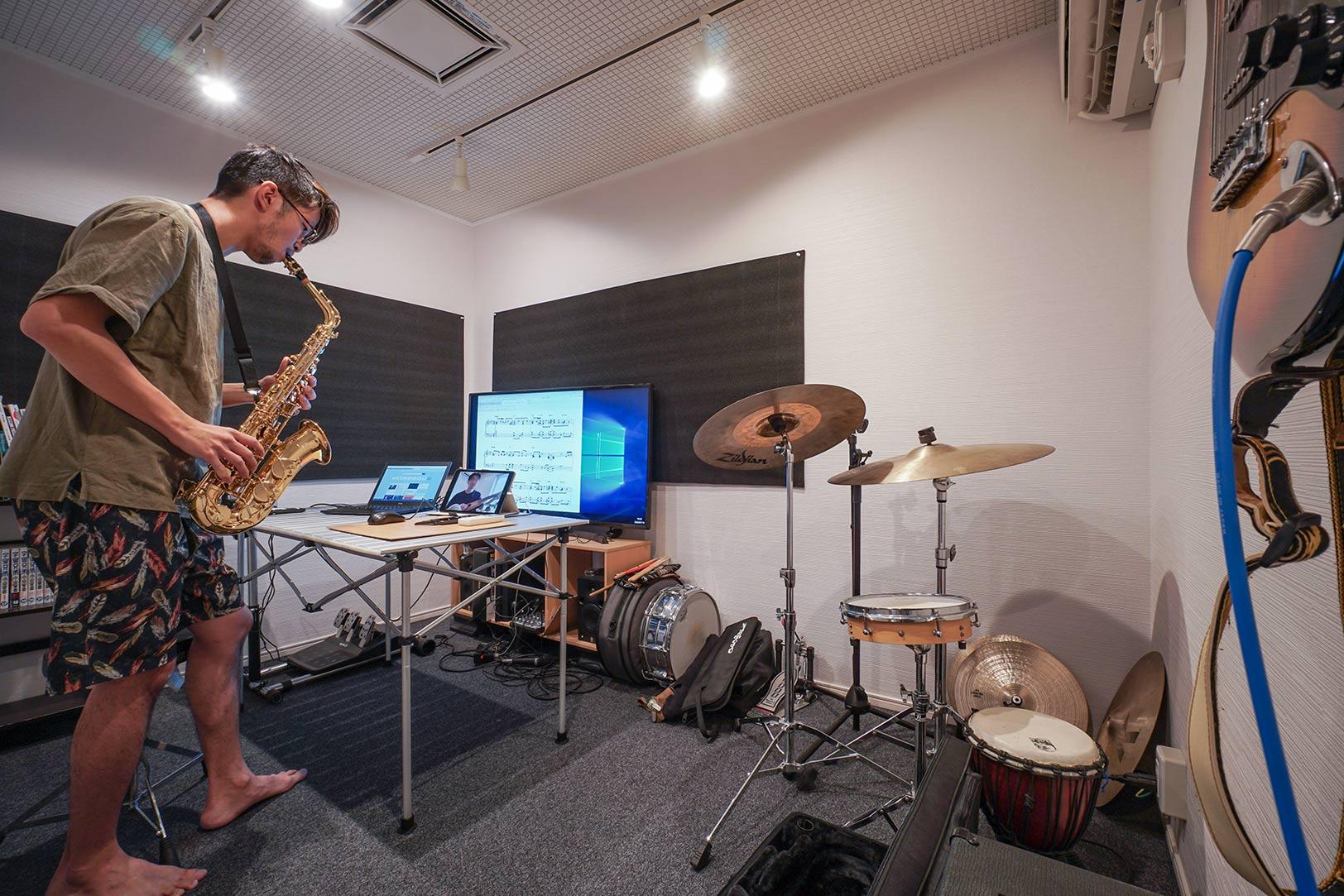 バイクから楽器演奏まで、多彩な趣味を持つ田中さんが家づくりの際に最優先したという防音室。かなり本格的に造ってあり、夜中にドラムを叩いても全然問題なし!とのこと。写真は、オンラインでの演奏セッションを楽しんでいるところ