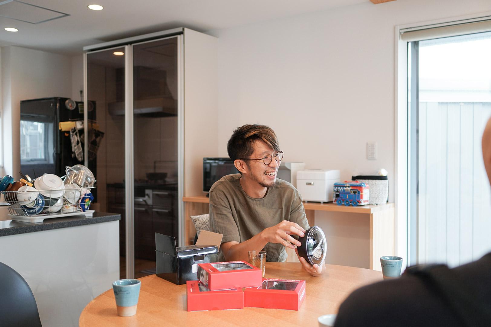 ネット通販でゲットしたバイクのライトのパーツを手にする田中さん。これから取り付ける予定とのこと